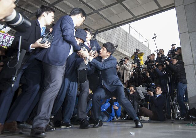 Choi Soon-Sil (C) is surrounded by the media as she arrives at the Seoul Central District Prosecutor's Office in Seoul on October 31, 2016