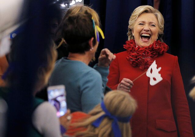 US Democratic presidential nominee Hillary Clinton holds a Halloween mask while joking with her staff on her campaign plane in Erlanger, Kentucky, US October 31, 2016.
