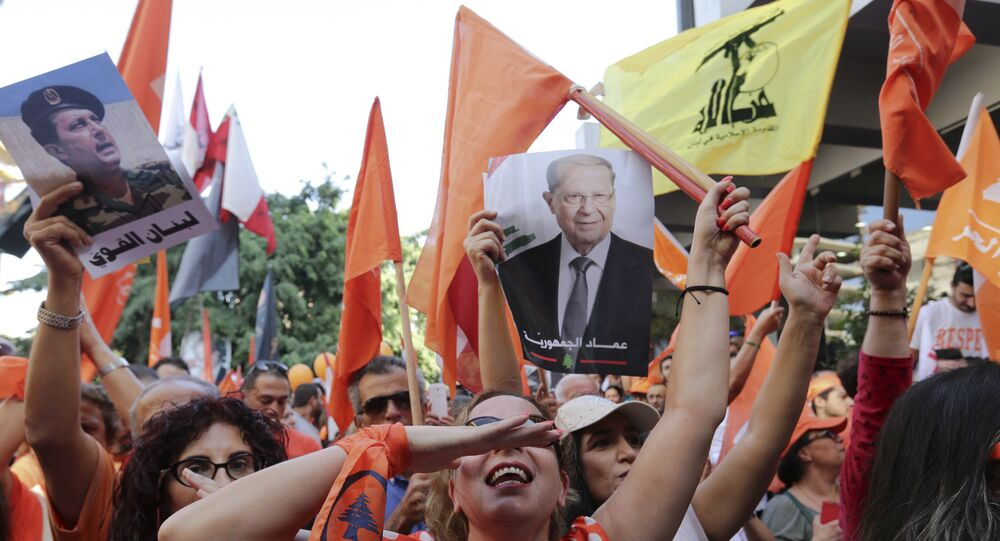 Supporters of Christian leader Michel Aoun hold his picture and Free Patriotic Movement, Lebanese flags and Hezbollah flag celebrate the election of the new President Michel Aoun, in Beirut, Lebanon, Monday, Oct. 31, 2016