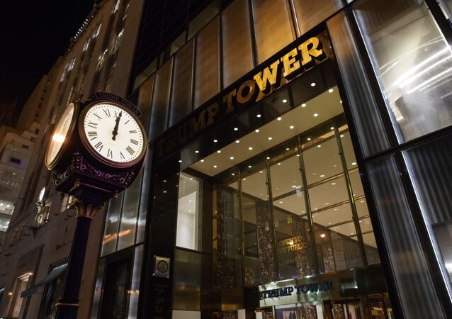 A clock sits outside of Trump Tower at midnight