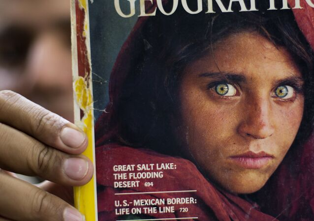 In this file photo taken on Wednesday, Oct. 26, 2016, Pakistan's Inam Khan, owner of a book shop shows a copy of a magazine with the photograph of Afghan refugee woman Sharbat Gulla