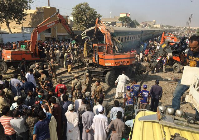Rescuers workers use heavy machinery on the car of a train which crashed outside Karachi, Pakistan November 3, 2016