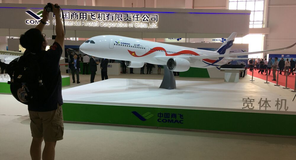 A man takes picture of the model of a widebody jet, which is planned to be developed by Commercial Aircraft Corporation of China (COMAC) and Russia's United Aircraft Corporation (UAC) at an air show, the China International Aviation and Aerospace Exhibition, in Zhuhai, Guangdong Province, China, November 2, 2016