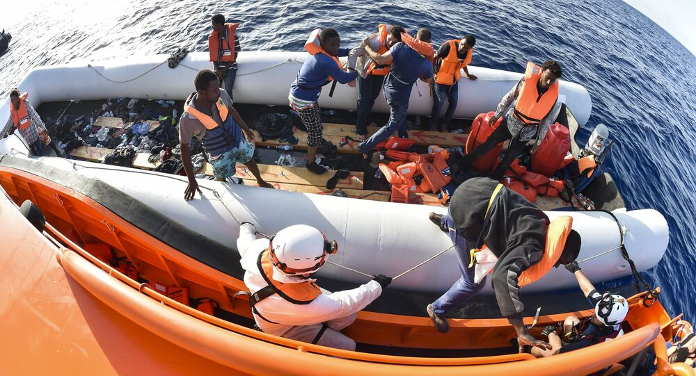 Men evacuate a rubber boat with the help of the crew of the Topaz Responder ship run by Maltese NGO Moas and the Italian Red Cross during a rescue operation of Migrants and refugees on November 3, 2016, off the Libyan coast in the Mediterranean Sea
