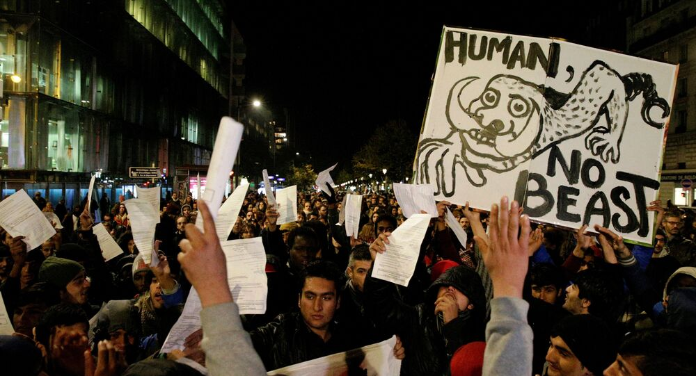 A man holds a placard reading Human not beast during a rally on November 2, 2016 in support of migrants living in a makeshift camp near the Stalingrad metro station in Paris, prior to its evacuation this week.