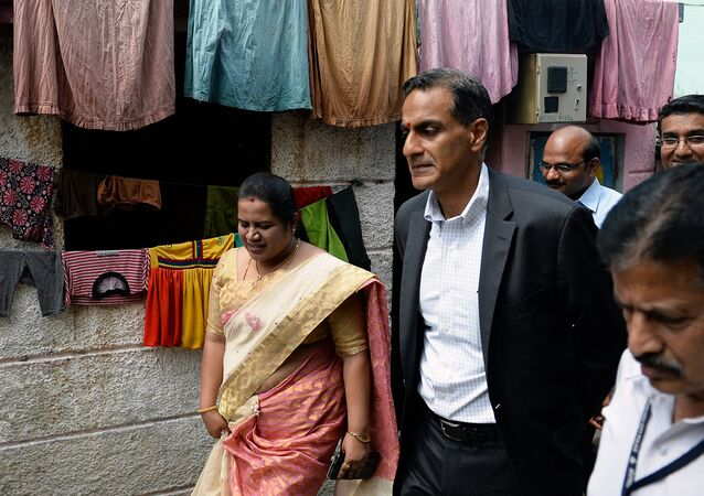 US Ambassador to India Richard R. Verma (centre R) walks through a slum in Bangalore on a visit to a drinking water project funded by USAID along with the local muncipal authority on November 3, 2015