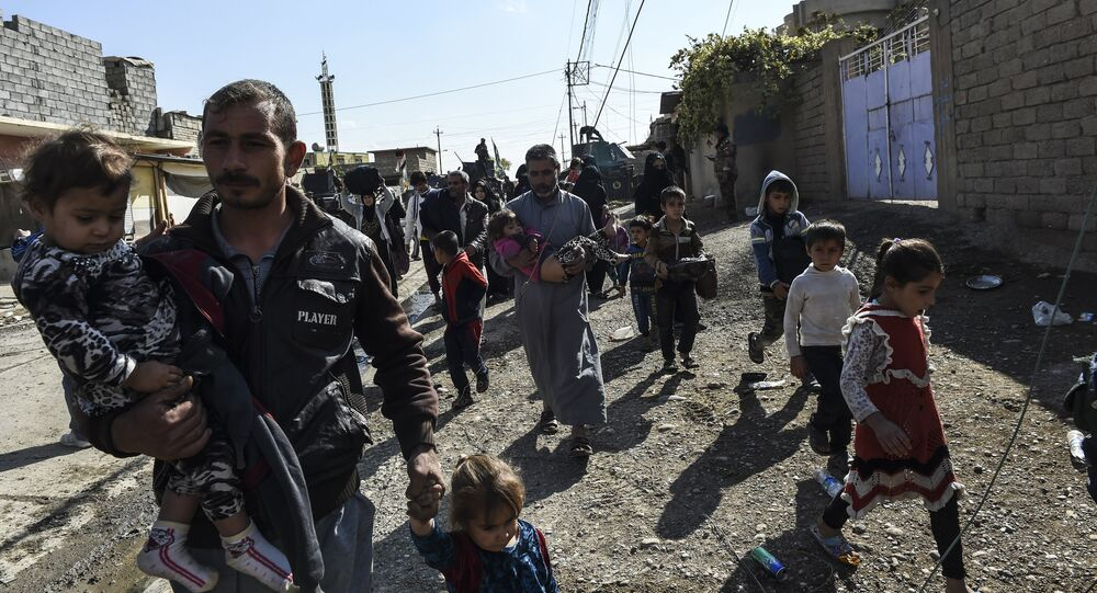 Iraqi civilians flee the village of Gogjali, a few hundred metres of Mosul's eastern edge, as clashes go on between Iraq army forces and jihadists of the Islamic State (IS) group to retake Mosul, the last Iraqi city under the control of IS, on November 2, 2016