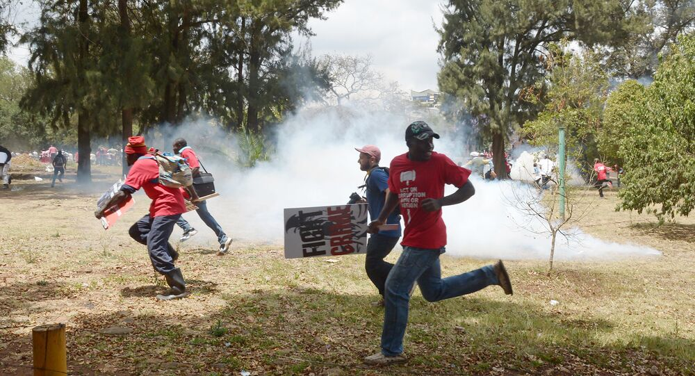 Kenyan human rights activists run from anti-riot police in Nairobi on November 3, 2016, during a demonstration calling for President Uhuru Kenyatta to have more effective actions against political corruption