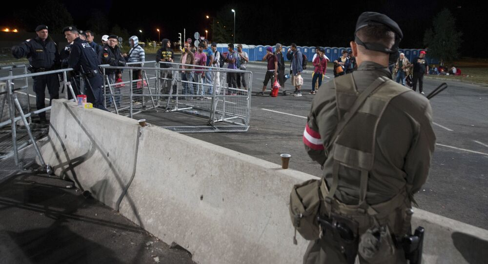 An Austrian Army soldier stands guard migrants lining up to get on a bus after they arrived at the border between Austria and Hungary near Heiligenkreuz, about 180 kms (110 miles) south of Vienna, Austria, Friday, Sept. 18, 2015