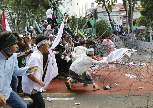 Muslim protesters pull razor wire blocking a road that leads to the presidential palace during a rally against Jakarta Governor Basuki Tjahaja Purnama in Jakarta, Indonesia, Friday, Nov. 4, 2016.