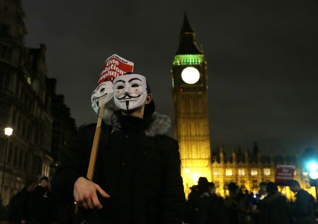 A masked demonstrator stands in Parliament Square during the Million Mask protest march in London on Thursday Nov. 5, 2015.