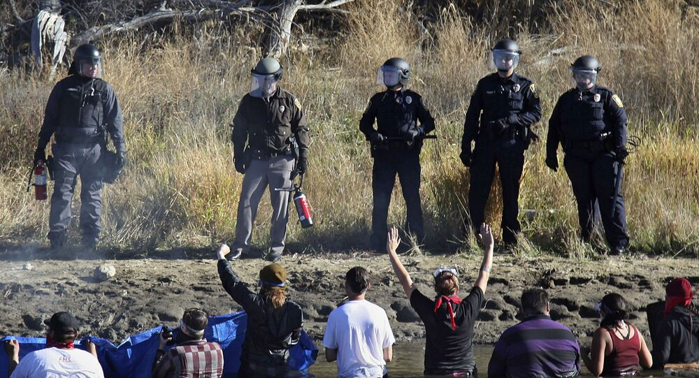 Dozens of protestors demonstrating against the expansion of the Dakota Access Pipeline wade in cold creek waters confronting local police, as remnants of pepper spray waft over the crowd near Cannon Ball, N.D., Wednesday, Nov. 2, 2016.