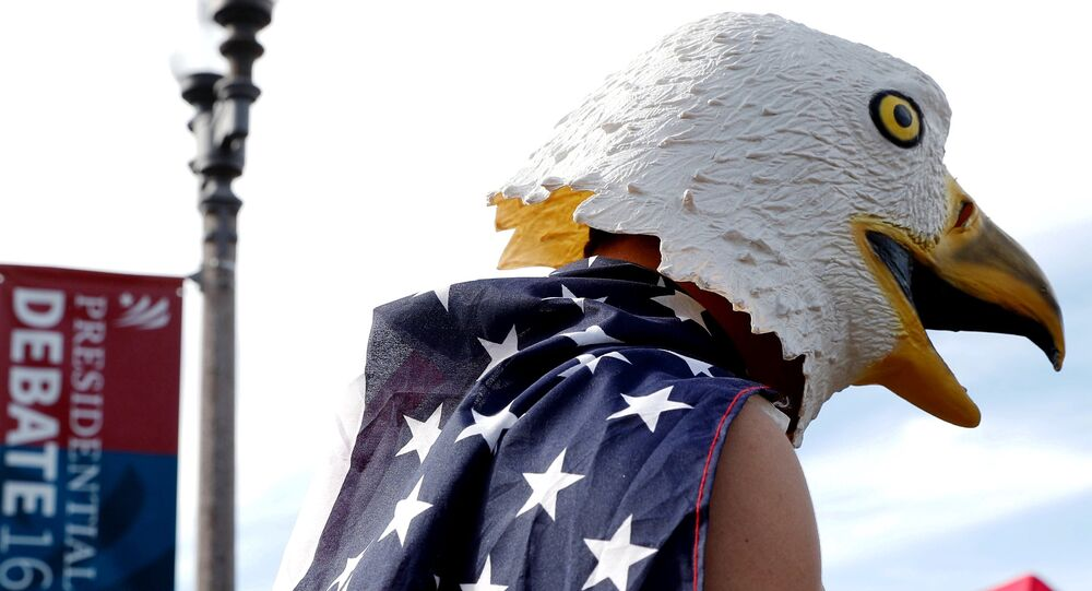 A man wears an eagle mask and is draped in a US flag outside of the event site of a U.S. presidential debate between Republican nominee Donald Trump and Democratic nominee Hillary Clinton at Washington University in St. Louis, Missouri, US, October 9, 2016.