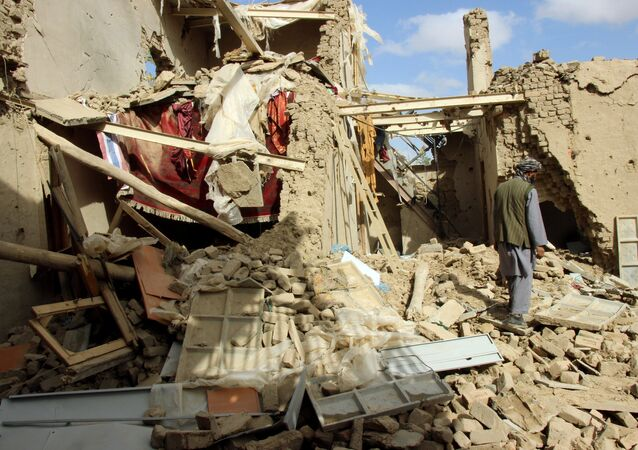 An Afghan man inspects a house destroyed during an air strike called in to protect Afghan and U.S. forces during a raid on suspected Taliban militants, in Kunduz, Afghanistan