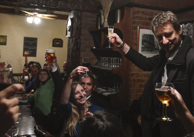 Newly elected French green party Europe-Ecologie-Les Verts (EELV) candidate for the 2017 presidential election Yannick Jadot (R) toasts as he celebrates with supporters after winning the EELV primaries, in a restaurant in Paris on November 7, 2016, Jadot won the second round of voting for the EELV primaries ahead of the 2017 French presidential election on November 7