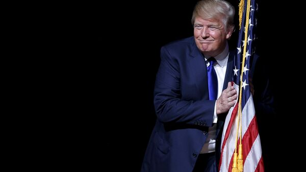 U.S. Republican presidential candidate Donald Trump hugs a U.S. flag as he takes the stage for a campaign town hall meeting in Derry, New Hampshire August 19, 2015 - Sputnik International
