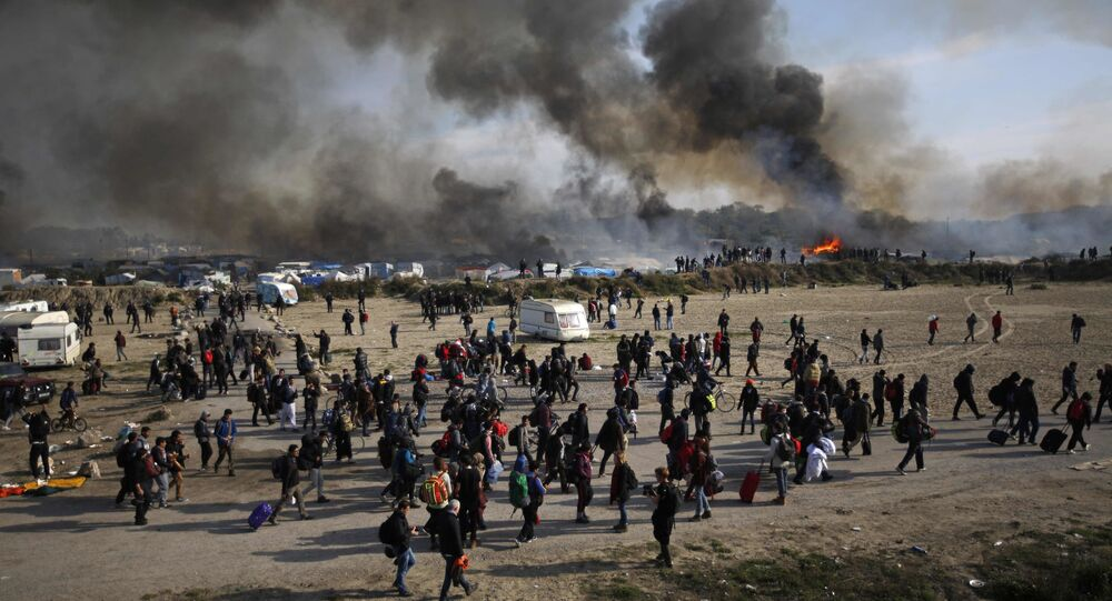 Oct. 26, 2016 file photo people walk past as thick smoke and flames rise from amidst the tents after fires were started in the makeshift migrant camp known as the jungle near Calais, northern France.