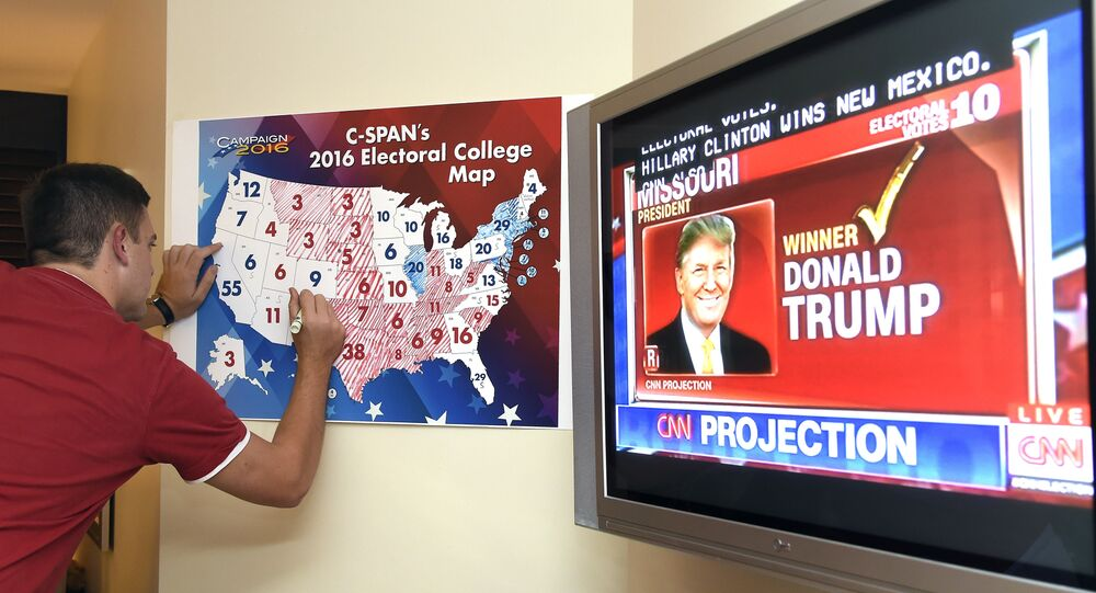 Jake Krupa colors in an electoral map as states projected for Republican presidential candidate Donald Trump or Democratic Presidential candidate Hillary Clinton at an election watching party in Coconut Grove, Florida, on November 8, 2016