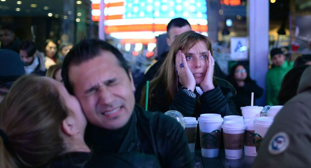 Supporters of Democratic candidate Hillary Clinton on Times Square in New York follow the preliminary vote results