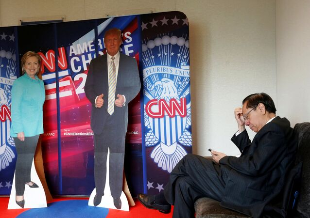 A man checks his smartphone beside cardboard cutouts of U.S. presidential candidates Hillary Clinton (L) and Donald Trump, at an event held by the American Chamber of Commerce in Hong Kong, China November 9, 2016.