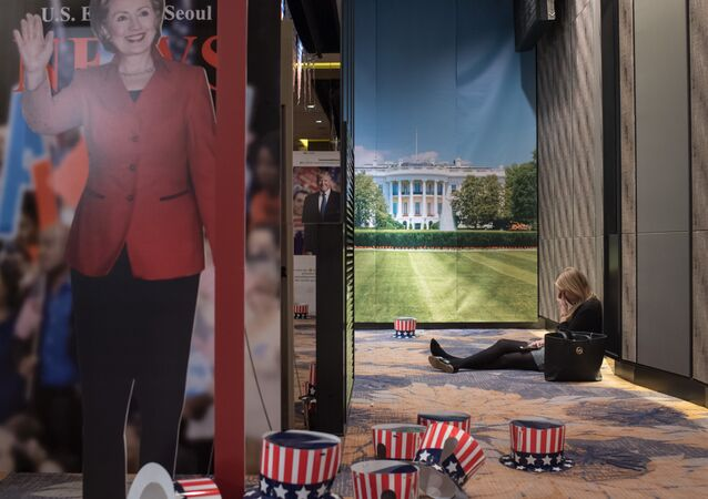 A woman sits on the floor behind a cut-outs of US presidential nominees Hillary Clinton and Donald Trump at an election event organised by the US embassy, at a hotel in Seoul on November 9, 2016