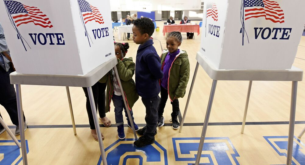 Children watch their mother vote during the U.S. general election in Greenville, North Carolina, US on November 8, 2016.