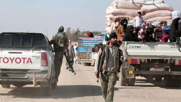 Syrian Democratic Forces (SDF) fighter walks near vehicles carrying people fleeing clashes in Tweila'a village and Haydarat area, north of Raqqa city, Syria November 8, 2016 - Sputnik International