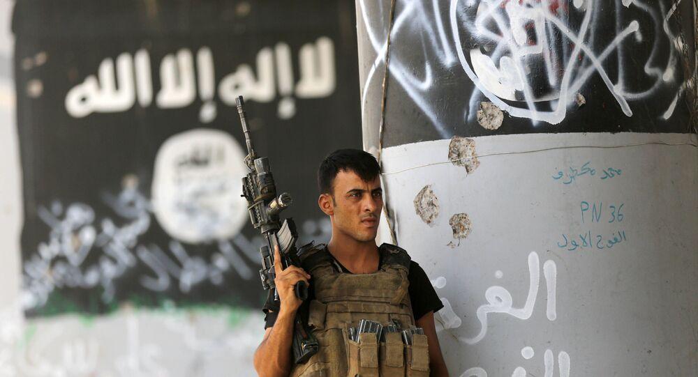 A member of Iraqi counterterrorism forces stands guard near Islamic State group militant graffiti in Fallujah, Iraq (File)