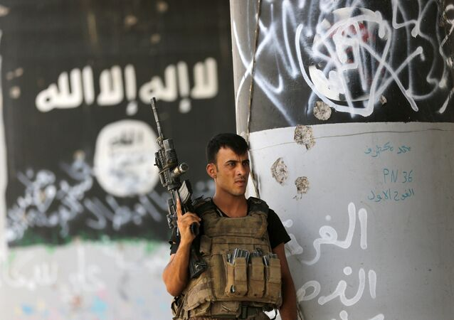 A member of Iraqi counterterrorism forces stands guard near Islamic State group militant graffiti in Fallujah, Iraq (File)