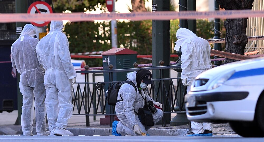 Police officers investigate at the front of the French embassy after two motorcyclists threw a hand granade injuring the guard early in central Athens on November 10, 2016