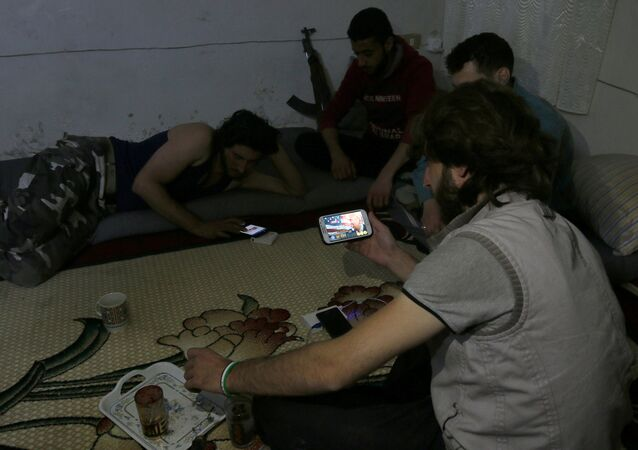 A Harakat Nour al-Din al-Zenki fighter watches news about Donald Trump's election as president on his smart phone in the rebel held beseiged area in Aleppo, Syria November 9, 2016