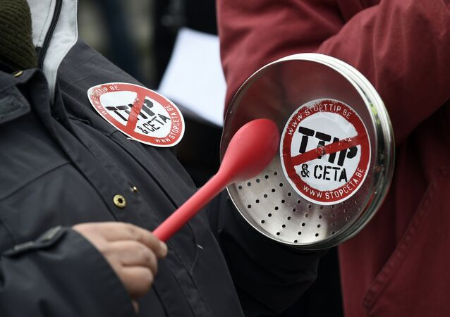 A demonstrator holds a lid with a sticker reading TTIP & CETA crossed during a protest against the EU-Canada Comprehensive Economic and Trade Agreement (CETA) at European Union Commission headquarters in Brussels on October 27, 2016.