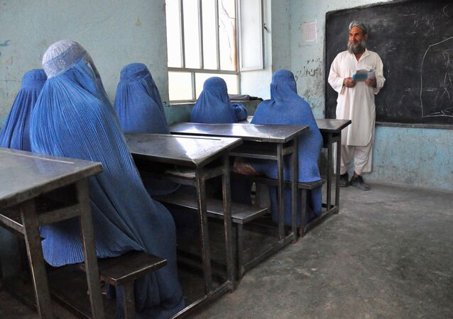 Afghan schoolgirls clad in burqas pay attention to their male teacher in the outskirts of Herat province on June 26, 2011