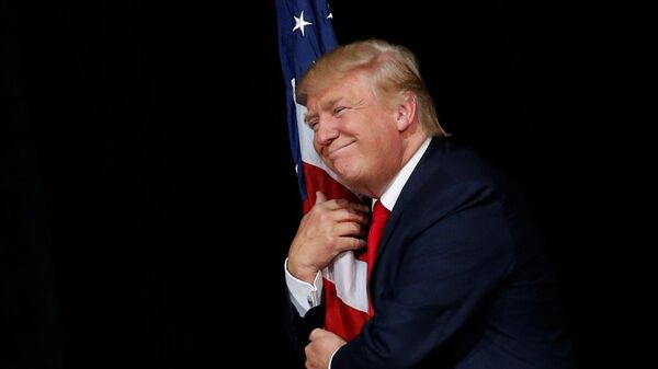 Donald Trump hugs a U.S. flag as he comes onstage to rally with supporters in Tampa, Florida, U.S. October 24, 2016 - Sputnik International