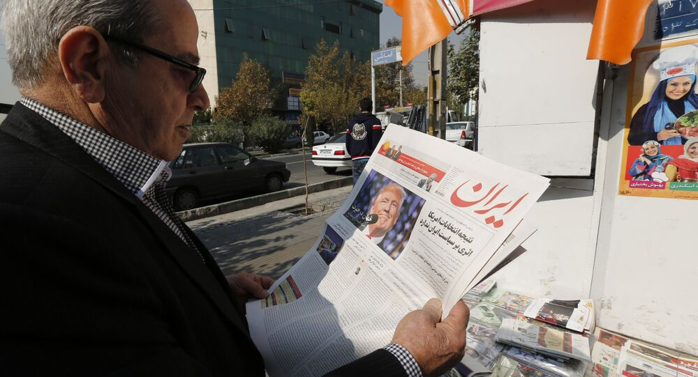 An Iranian man holds a local newspaper displaying a portrait of Donald Trump a day after his election as the new US president, in the capital Tehran, on November 10, 2016