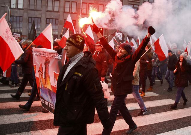 Protesters light flares and carry Polish flags during a rally, organised by far-right, nationalist groups, to mark the anniversary of Polish independence in Warsaw, Poland, November 11, 2016