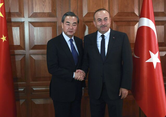 Chinese Foreign Minister Wang Yi (L) and Turkish Foreign Minister Mevlut Cavusoglu shake hands before a meeting in Ankara, on November 13, 2016.