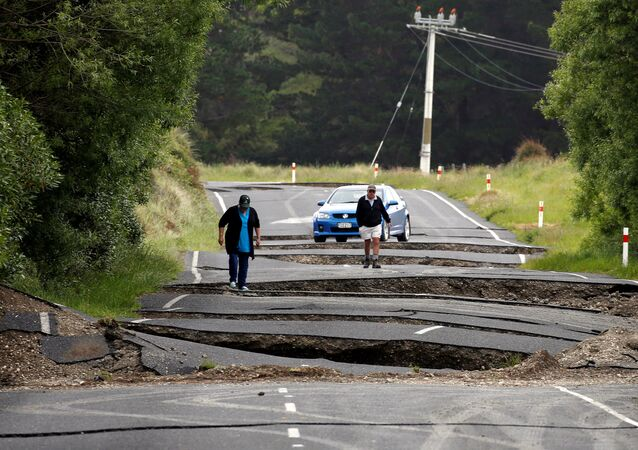 Local residents Chris and Viv Young look at damage caused by an earthquake along State Highway One, south of the township of Blenheim on New Zealand's South Island, November 14, 2016.