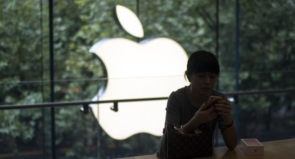 A Chinese customer sets up her new iPhone 7 during the opening sale launch at an Apple store in Shanghai