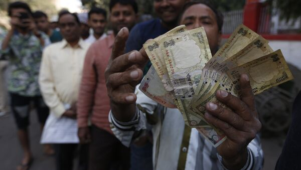 An Indian man displays Indian currency notes of 1000 and 500 rupees as he stands in queue to exchange or deposit discontinued currency notes outside a post office in Ahmadabad, India, Thursday, Nov. 10, 2016. - Sputnik International