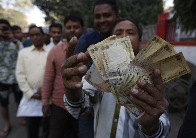 An Indian man displays Indian currency notes of 1000 and 500 rupees as he stands in queue to exchange or deposit discontinued currency notes outside a post office in Ahmadabad, India, Thursday, Nov. 10, 2016.