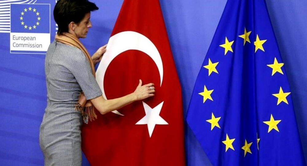A woman adjusts the Turkish flag next to the European Union flag before the arrival of Turkish Prime Minister Ahmet Davutoglu (unseen) at the EU Commission headquarters in Brussels January 15, 2015.
