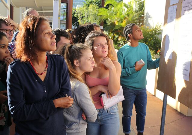 Students look at a board displaying the results of the baccalaureat exam (high school graduation exam) on July 5, 2016 at the Moulin Joli high school in La Possession, in the French overseas department of La Reunion