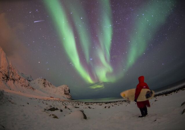 A surfer looks at northern lights ( aurora borealis ) at the snow covered beach of Unstad, on Lofoten Island, Arctic Circle, on March 9, 2016