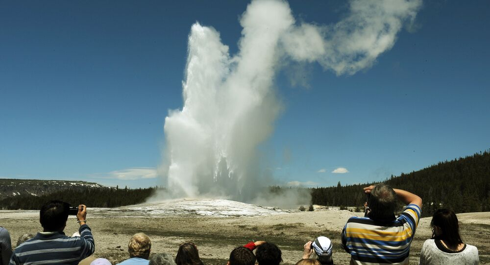Tourists watch the 'Old Faithful' geyser which erupts on average every 90 minutes in the Yellowstone National Park, Wyoming on June 1, 2011