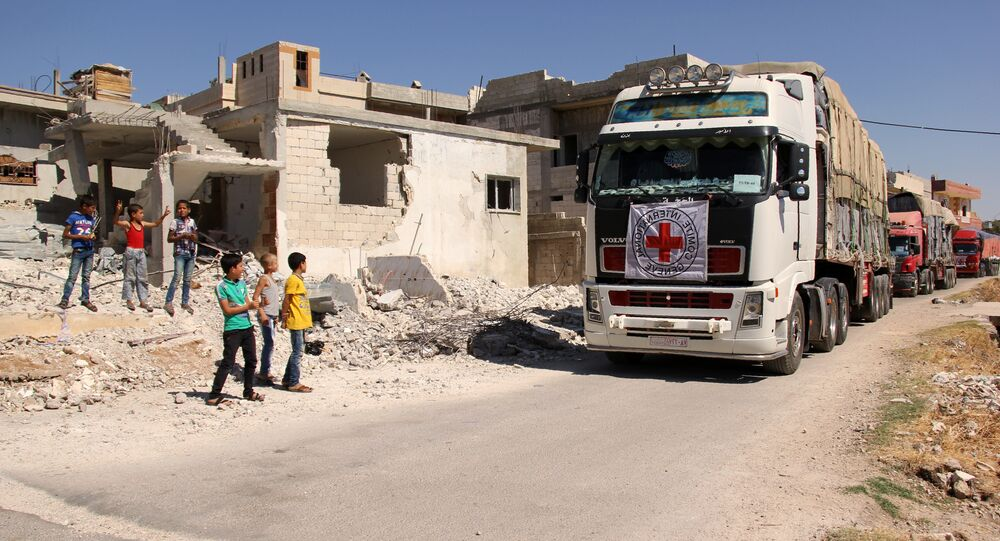 Syrian children stand on the side of a road watching a 48-truck convoy from the ICRC, SARC and UN driving through the Syrian rebel-held village of Teir Maalah, on the northern outskirts of Homs in central Syria, as it heads to the besieged town of Talbisseh on July 26, 2016