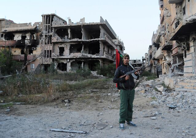 In this Feb. 23, 2016 file photo, a civilian fighter holding the Libyan flag stands in front of damaged buildings in Benghazi, Libya. Amnesty International, an international rights group expressed alarm Friday, Sept. 30, 2016