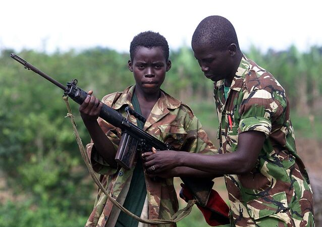 A fourteen year old child soldier for the Sierra Leone Army, Abu Kamara, left, is helped with his British self Loading rifle (SLR) by another soldier while protecting the small town of Ropath near Masiaka, 55 km east of the capital Freetown, Tuesday May 23, 2000