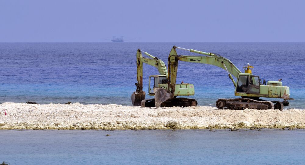 Two excavators are pictured at a construction site on Taiping island in the Spratly chain in the South China Sea on March 23, 2016