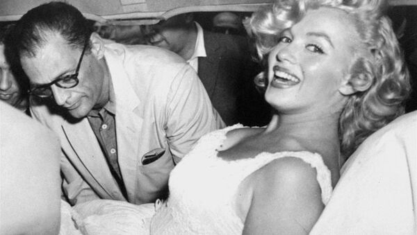 Marilyn Monroe is made comfortable in a car by her husband, playwright Arthur Miller, following her release from Doctors Hospital, New York City, August 10, 1957. - Sputnik International